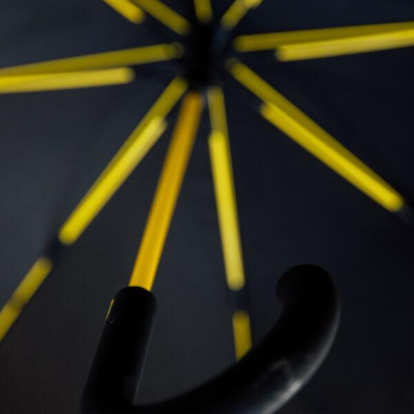 Melns lietussargs ar dzelteniem spieķiem